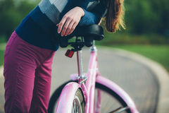 Young woman standing in park with bicycle Stock Images