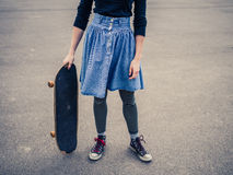 Young woman standing in the park with a skateboard Stock Images