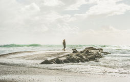 Young woman standing on pier and enjoying stormy sea Stock Image