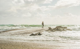 Young woman standing on pier and looking at stormy sea Royalty Free Stock Photography
