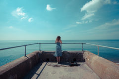 Young woman standing on a pier by the ocean Stock Photo