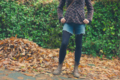 Young woman standing by pile of leaves in autumn. A young woman is standing by a pile of leaves in the autumn stock photos
