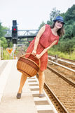 Young woman standing on platform and waiting for train. Young woman in red dress and blue hat holding a basket and waiting on platform at train station Royalty Free Stock Photography
