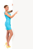 Young woman standing and pointing at banner. Stock Photography