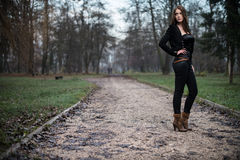 Young woman standing and posing at the forest. Young woman i jacket standing and posing Royalty Free Stock Image