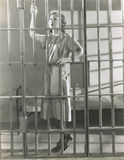Young woman standing in prison cell Stock Photo