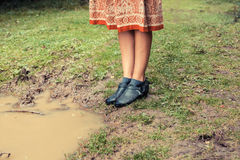 Young woman standing by a puddle in the forest Stock Photo