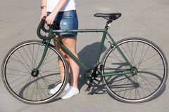 Young woman standing on the road next to green bike Stock Photos