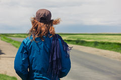 Young woman standing by roadside in the country Royalty Free Stock Photo