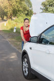 Young woman standing at the roadside and looking under the hood Stock Photo