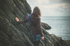 Young woman standing by a rock on the coast. A young woman is standing by a rock on the coast and is admiring the sea on a cloudy and cold day of autumn Stock Photos