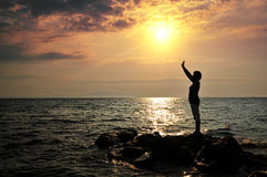 Young woman  standing on rock in sea Stock Photography