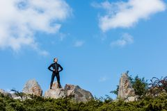 Woman standing on rocks with arms akimbo. Young woman standing on rocks with arms akimbo and looking away stock photography
