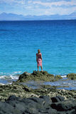 Young woman standing rocks, looking out to sea Stock Photo