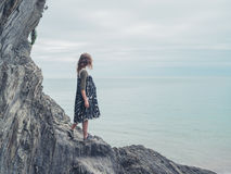 Young woman standing on rocks and looking at sea Royalty Free Stock Images