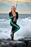 Young woman standing on the rocks wearing neoprene scuba suit and holding fishing spare. Royalty Free Stock Photography