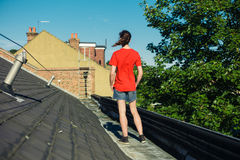 Young woman standing on a roof Stock Photo