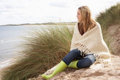Young Woman Standing In Sand Dunes. Wrapped In Blanket Royalty Free Stock Image