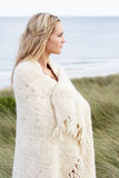 Young Woman Standing In Sand Dunes. Wrapped In Blanket Royalty Free Stock Images
