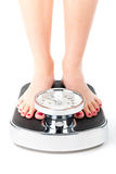 Young woman standing on a scale. Diet and weight, young woman standing on a scale, only feet to be seen royalty free stock image