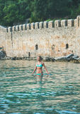 Young woman standing in sea at beach near fortress wall Royalty Free Stock Images