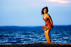 Young woman standing on seacoast on sunset Stock Photo