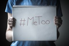 Young woman standing in shadow holding  notepad into the light with  MeToo written on the  page. Close-up of young woman holding notepad against  her chest with Royalty Free Stock Photo