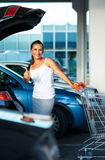 Young woman standing with shopping cart and thumb up near the ca Stock Photography
