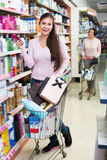 Young woman standing with shopping cart Royalty Free Stock Images