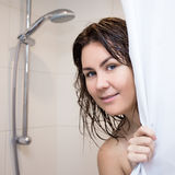 Young woman standing in shower and covering herself with curtain Royalty Free Stock Photography
