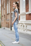 Young woman standing on sidewalk Royalty Free Stock Images