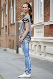 Young woman standing on sidewalk, smiling Royalty Free Stock Image