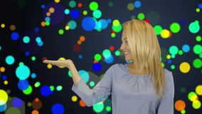 Young woman standing smiling holding her hand showing something on the open palm, concept of advertisement product. Empty copy space, glow confetti background stock video