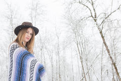 Young woman standing in snow with bohemian style hat and blanket. Young woman in the snow wearing a bohemian style blanket and hat during a winter storm Stock Images