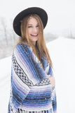 Young woman standing in snow with bohemian style hat and blanket. Young woman in the snow wearing a bohemian style blanket and hat during a winter storm Royalty Free Stock Photos