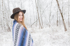 Young woman standing in snow with bohemian style hat and blanket. Royalty Free Stock Images