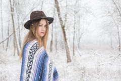 Young woman standing in snow with bohemian style hat and blanket. Young woman in the snow wearing a bohemian style blanket and hat during a winter storm Royalty Free Stock Photo