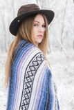 Young woman standing in snow with bohemian style hat and blanket. Young woman in the snow wearing a bohemian style blanket and hat during a winter storm Stock Photography