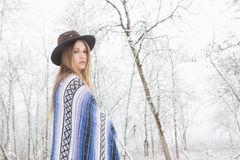 Young woman standing in snow with bohemian style hat and blanket. Young woman in the snow wearing a bohemian style blanket and hat during a winter storm Royalty Free Stock Image