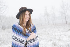 Young woman standing in snow with bohemian style hat and blanket. Young woman in the snow wearing a bohemian style blanket and hat during a winter storm Royalty Free Stock Images