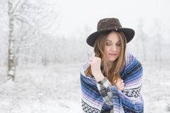Young woman standing in snow with bohemian style hat and blanket. Young woman in the snow wearing a bohemian style blanket and hat during a winter storm Stock Photos