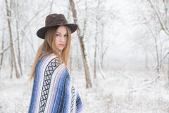 Young woman standing in snow with bohemian style hat and blanket. Young woman in the snow wearing a bohemian style blanket and hat during a winter storm Stock Image