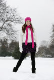A young woman standing in the snow, smiling Stock Image