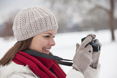 A young woman standing in the snow, taking a photograph Stock Photography