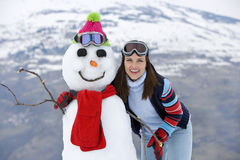Young woman standing by snowman, smiling, portrait, mountain range in background Royalty Free Stock Photos