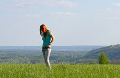Young woman standing on spring meadow Royalty Free Stock Images