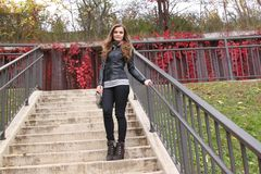 Young woman standing on stairs with purse and boots. Young woman with long hair, natural makeup, standing on stairs with fall colors in the background, wears Royalty Free Stock Photos