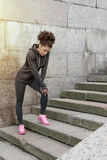 Young woman standing on stairs. Taking a short break during workout outdoors royalty free stock images