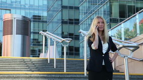 Young woman standing on the stairs and talking on a cellular phone stock footage