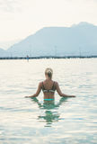 Young woman standing in still morning sea waters in Alanya. Young beautiful slavian woman tourist standing in still morning sea waters at beach near ancient Stock Photography